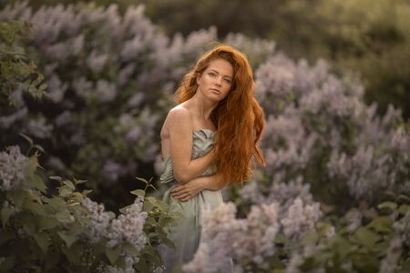 Woman with long red hair on a background of bushes with lilac flowers