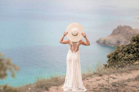 A woman in a long white dress during the honeymoon on a walk in the mountains above the sea.
