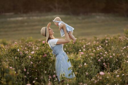 Young beautiful mother with a child stands in an agricultural field with a flowering rose.