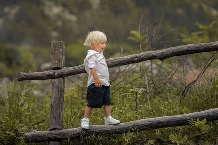 A 4-year-old child climbs a wooden old fence. Standard-Bild
