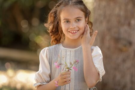 Girl, 12, with pigtails close-up holds a flower in her hands Standard-Bild
