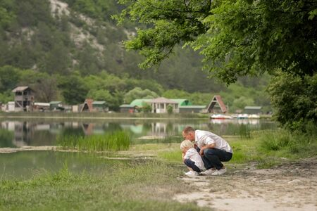 The man and his son are squatting on a rum of water and looking for frogs