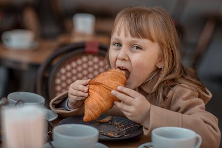 Girl eats croissant in street cafe in autumn.