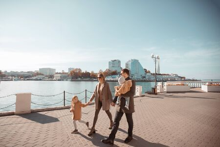 A young happy family of four walks in the spring on a sunny day. Husband and wife with two children Standard-Bild