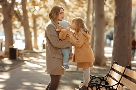 Mother and child on a walk in a public park hugs and kisses