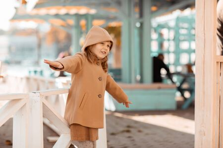 Baby girl has fun and plays on a sunny autumn day in the playground in a public park.
