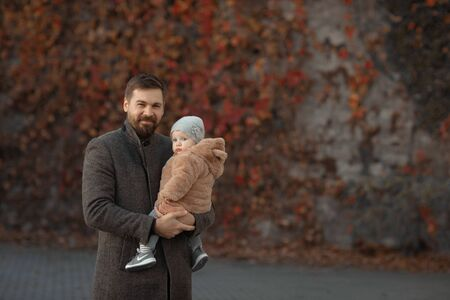 Father holds his daughter in his arms during a walk in the park in the fall.