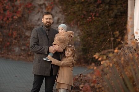 The father holds his youngest daughter in his arms while the eldest hugs him and stands next to him