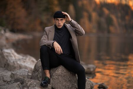 One male model dressed with a stylish coat and a fall cap outside. Standard-Bild