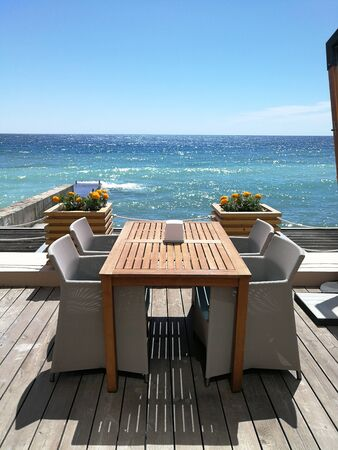 Relaxation zone on the coast of public beach. Dining area with a panorama of the sea bay Standard-Bild
