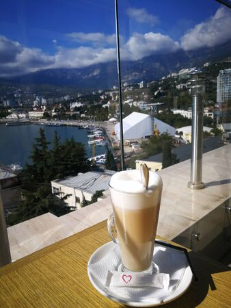A cup of coffee close-up against the backdrop of the sea bay. Standard-Bild