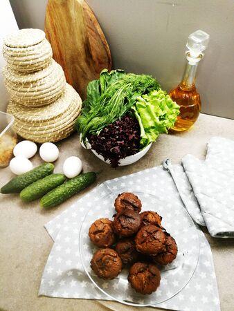 Burnt baked pastries on a napkin near fresh green vegetables.