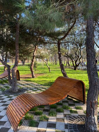 Modernist bench to rest from wooden bars in public fghrt in the city.