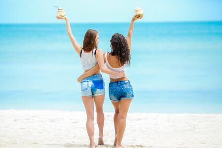 Two girls with coconut cocktails. Two best friends together have fun and relax on the coast of the tropical ocean