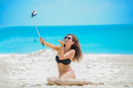 Woman takes a selfie in the background of the ocean. The girl in the swimsuit is young and beautiful with a selfie stick in her hands posing and photographed