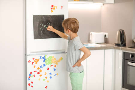A 8-year-old schoolboy writes white chalk on a magnetic black board attached to a fridge.