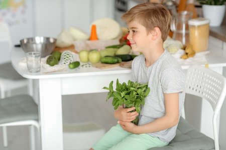 The child puts vegetables on the table and prepares a salad.