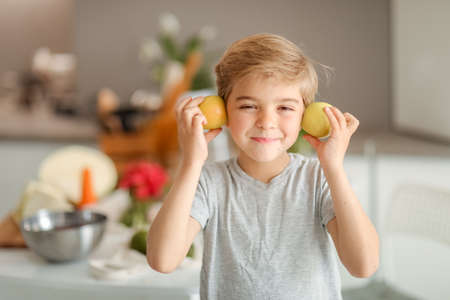 The boy in the kitchen is amused and fooled around with two apples in his hand 免版税图像