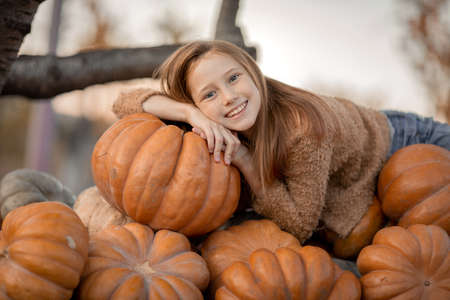 A girl lies on a trolley with ripe pumpkins