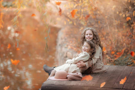 Two sisters sit on a wooden pier in the autumn on the shore of the lake