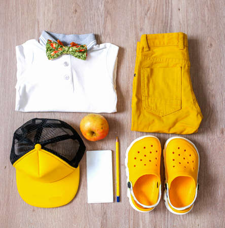 Stylish set of a little boy with dominant yellow colors and accessories.