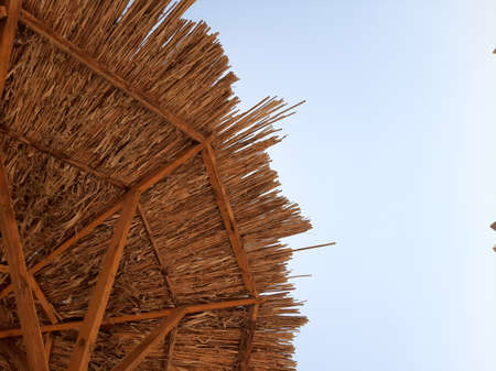 A projection of a straw canopy against a blue sky.