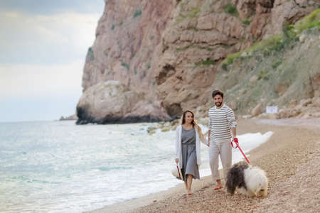 Happy young couple walking with big dog on the beach in summer. 免版税图像