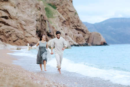 Frame shoot of couple walking on beach together in love holding each other by hand 免版税图像