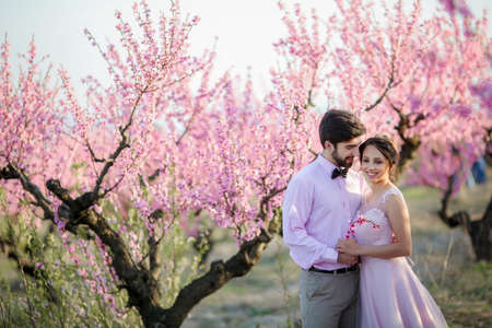 Beautiful wedding couple in the gardens of a blossoming peach 免版税图像
