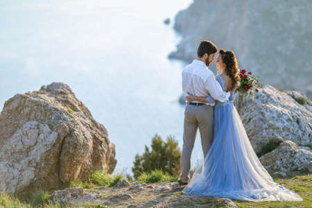A Stylish newlyweds cuddle in nature, on the background of rocks and cliffs