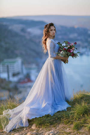 Beautiful bride in wedding dress on the mountain top. Stunning young bride with curly hair and a bouquet of flowers in her hands. Wedding day. .Beautiful portrait of a bride without a bridegroom. 免版税图像