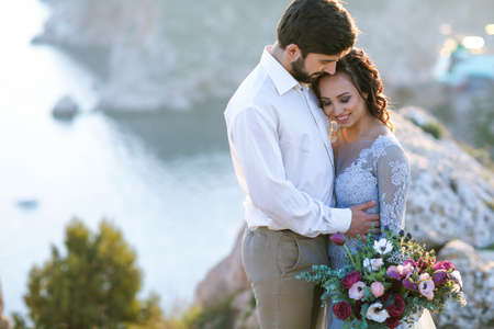 Young Wedding couple. Beautiful bride in fashion wedding dress kissing and hugging near rocks on beautiful landscape.Wedding day. .A beautiful bride portrait at sea view.