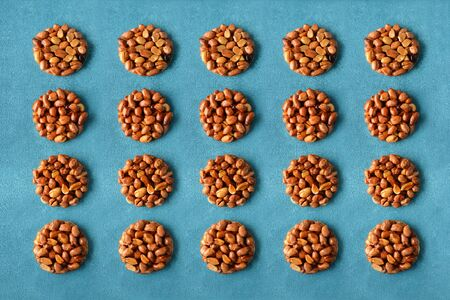 Pattern of tasty eastern sweets kozinaki made from peanuts and honey on a blue background.