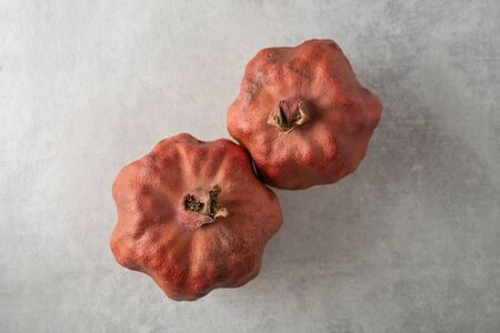 An old ugly dried-up red pomegranates fruits on a gray background. The Central composition, top view. Horizontal orientation. Close up.