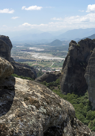 Picturesque valley in the mountains with rocks and trees, overlooking the village and fields with agricultural plants, summer, day, Meteora, Greece Stock Photo