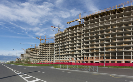 The construction of houses along the new asphalt road, next to construction equipment, cranes, on the Gulf of Finland, Residential complex Sail, the Baltic Boulevard, Krasnoselsky district, Saint Petersburg