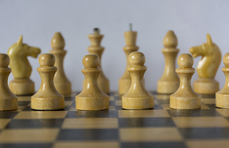 chessman: wooden white chess pieces, chessman, pawn, knight, castle, queen, king stand on a chessboard in the initial position, in the foreground pawns Stock Photo