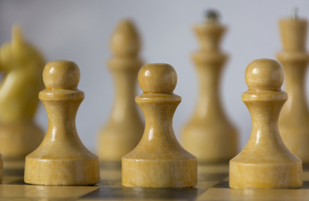 chessman: white wooden chess pieces, chessman, pawn, knight, castle, queen, kingstand on a chessboard in the initial position, in the foreground pawns