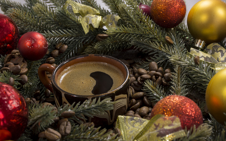 black strong coffee in a Cup among coffee beans, Christmas fir branches and colored red, yellow balls, ribbon, decor, coziness