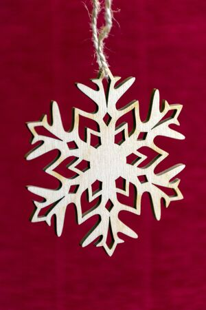 cymbol: snowflake hanging on a rope, the twine on a red background, new year, Christmas, holiday