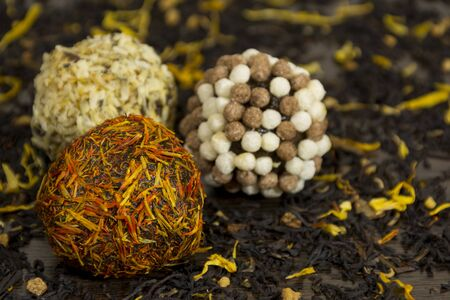 chocolate balls coated in yellow and orange petal flowers and nuts, confectionery, delicious, dessert, tea leaves