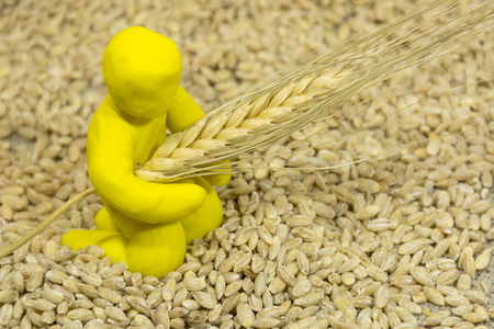 yellow clay figure of man sitting among the grains and holds the ear of wheat in hands