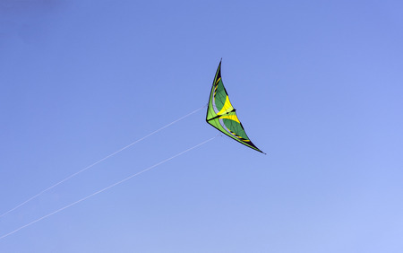 wedgeshaped yellow with green kite floating in the blue sky, Sunny day Stock Photo