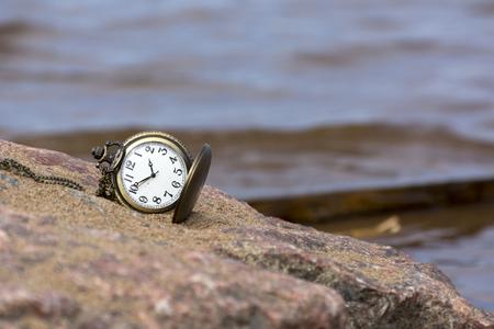 Relógio de bolso em pedra redonda sobre um fundo de água do mar Foto de archivo