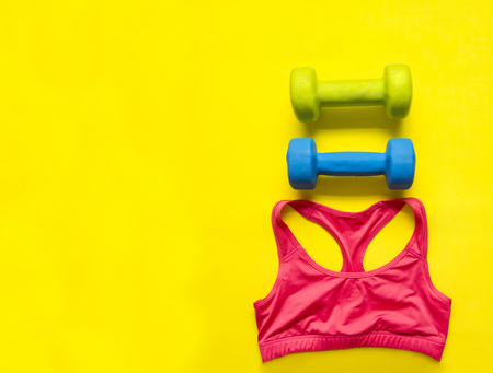 dumbbelsl and red sports tank top on yellow background,flat lay, sportswear top view,  Stock Photo