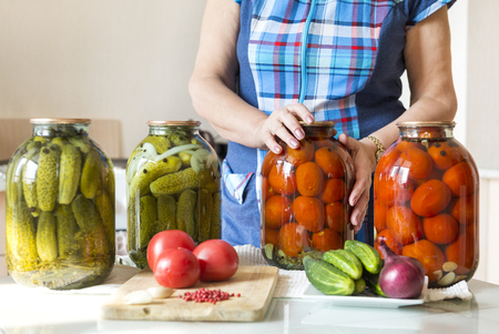 woman in blue plaid tunic in the kitchen next to the table on the table are jars of pickled, salted tomatoes and cucumbers, food, on the table are fresh tomatoes, cucumbers, onions, garlic, vegetables,