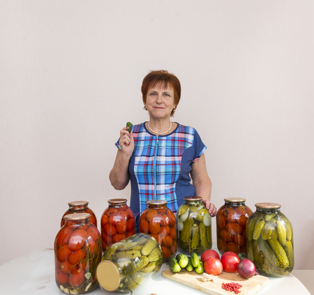 woman in a blue checkered tunic has a cucumber in the kitchen next to the table. on the table are jars of pickled, salted tomatoes and cucumbers, on the table are fresh tomatoes, cucumbers, onions, garlic, vegetables, food