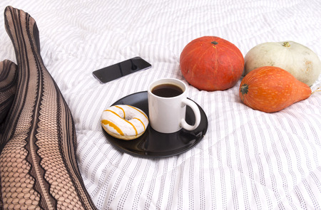 Cup of coffee, donut with icing on a plate, 3 pumpkins on a blanket, phone, gadget, women's feet,