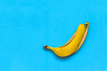 yellow skin of a banana against a blue background,  fruit