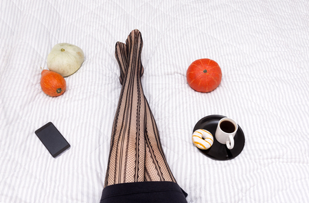 Cup of black coffee, Donat with white glaze and yellow stripes on the plate, women's feet in black lace stockings, pumpkins, phone on a white blanket Stock Photo